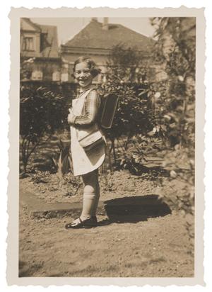 Helga Becker-Leeser vor einer Hecke in Kleid mit kleiner Tasche und Schulranzen.