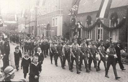 Verzierte Innenstadt, links im Bild mehrere Jungen, mittig ein Musikzug bestehend aus mehreren Gruppen.