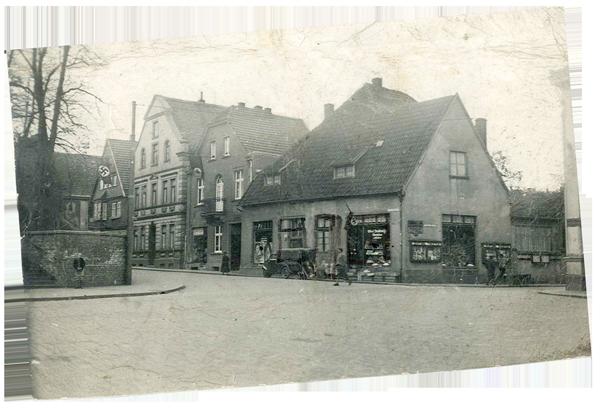 Einstöckiges Eckgebäude mit Spitzdach und Schaufenster. Links davon zwei- bzw. dreistöckige Gebäude, denen gegenüber eine Mauer.