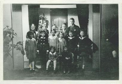 Aufnahme von 14 Kindern vor einem Fenster mit brennendem Chanukka.