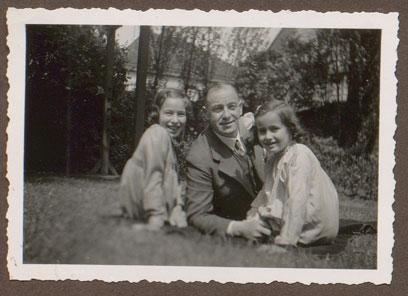 Hermann, Helga und Ingrid Leeser auf einer Wiese liegend/hockend. Im Hintergrund Gebäude und Grün.