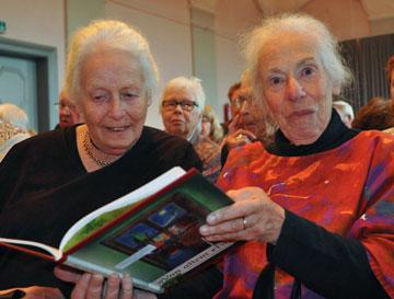 Helga Leeser hält ein geöffnetes Buch und schaut in die Kamera, Ingrid Leeser sieht in das Buch. Dahinter einige ebenfalls sitzende Menschen.