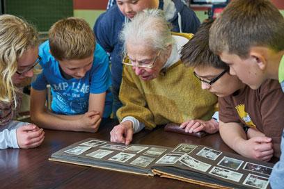 Helga Leeser blättert zusammen mit einigen konzentrierten Kindern in einem Fotoalbum an einem braunen Tisch.