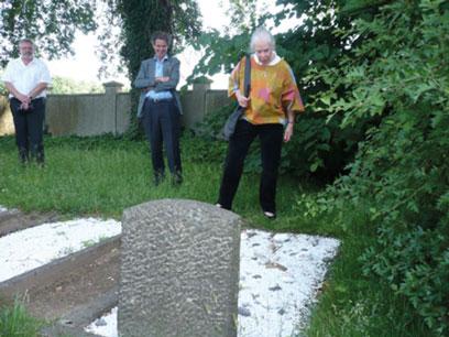 Helga Leeser auf einer Wiese ein einem Grab mit kniehohem Grabstein und Steinen im Vordergrund. Links daneben weitere Personen, rechts Sträucher.