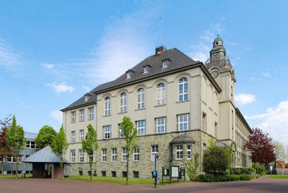 Großes dreistöckiges Gebäude, der untere Teil mit Stein, oben verputzt. Die Fenster des obersten Stockes sind deutlich größer als die der unteren Etagen.