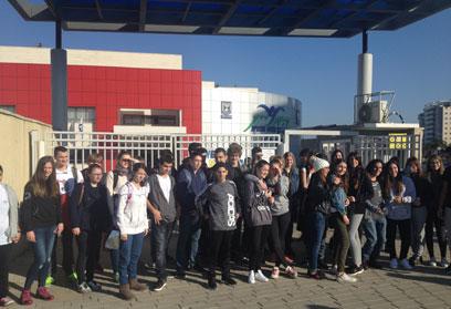 Schulgruppe vor dem Tor eines modernen Gebäudes.