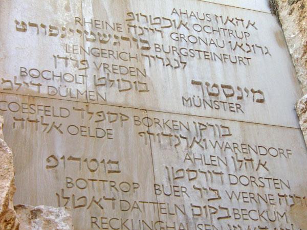 Tafel aus hellem Stein, darin verschiedene Stadtnahmen in hebräischen und lateinischen Buchstaben eingemeißelt.^