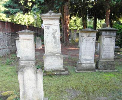 Mehrere Grabsteine auf teils grünem, teil unbewachsenem Boden. Im Hintergrund hohe Bäume, links eine Mauer aus roten Ziegeln.