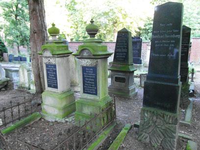 Links zwei umzäunte Grabsteine mit hellem aber bemoostem Stein und dunklen Tafeln, in der Umgebung dunkle Säulen auf hellem Stein.