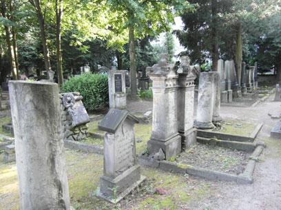Mehrere helle Grabsteine und halbe Säulen, drumherum Bäume. Vor den Grabsteinen keine Bepflanzung.