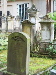 Grabstein mit gebogener Spitze, leicht bemoost, dahinter weitere helle Grabsteine und ein Gebäude.