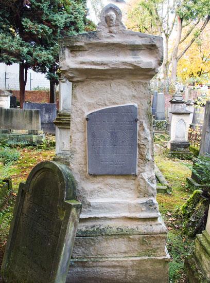 Heller Grabstein mit angebrachter dunkler Platte mit hebräischer Inschrift. Links lehnt eine Dunkle gewölbte Platte mit hebräischer Inschrift an.