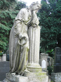 Statue einer trauernden Frau mit Kranz in der rechten Hand, die linke Hand lehnt mit dem Ellenbogen auf eine runde Säule, auf deren Hand der Kopf gestützt ist. Im Hintergrund Bäume und Grabsteine.