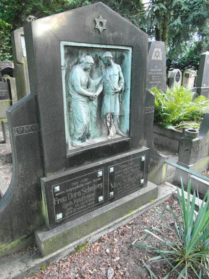Großer Grabstein mit oxidiertem Kupferrelief von einer Frau und einem Mann. Darüber ein Davidstern, darunter die Namen der Verstorbenen.