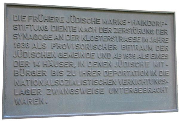 """Dunkle rechteckige Tafel mit Großbuchstaben. """"Die frühere jüdische Marks-Haindorf-Stiftung diente nach der Zerstörung der Synagoge an der Klosterstraße im Jahre 1938 als provisorischer Betraum der jüdischen Gemeinde und ab 1939 als eines der 14 Häuser, in denen jüdischen Mitbürger ab 1939 bis zur ihrer Deportation in die nationalsozialistischen Vernichtungslager zwangsweise untergebracht waren."""""""