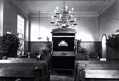 Schwarz-weiß-Fotografie mit Bänken links und rechts, über dem Mittelgang ein kleiner Kronleuchter, vorne ein Toraschrein.