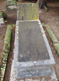 Im Hintergrund eine bemooste Grabsteinplatte, davor ein großes rechteckiges hellgraues Steinkenotaph mit dunkelgrauer Platte darauf. Umrandet von bemoosten Steinen.